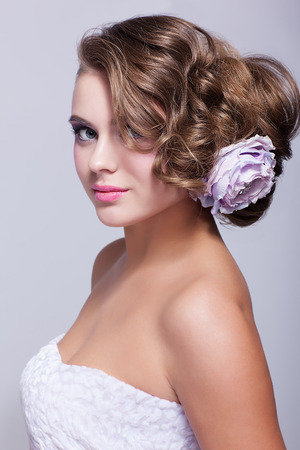 pion: Portrait of beautiful young woman on gray background with artificial pion flower in hairs