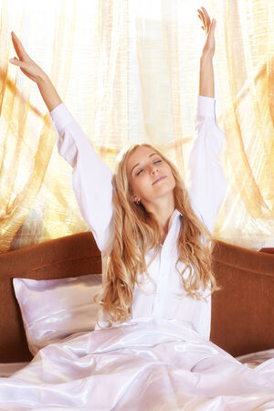 Young beautiful blonde in the bed at morning time stretching hands up with closed eyes photo