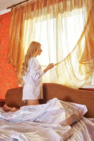 Young beautiful blonde in the bed at morning time near window under Sun rays photo
