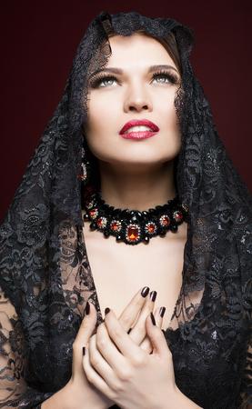 mujeres orando: Mujer hermosa joven en vestido negro con velo en color oscuro fondo marsala rojo Foto de archivo