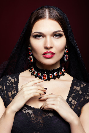luxe: Young beautiful woman in black dress with veil on dark red marsala color background Stock Photo
