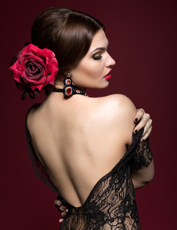 Young beautiful woman in black dres and black rose flower in hair from back side on dark marsala color background