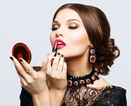 Makeup of young beautiful brunette woman in black dress on gray background with lipstick and mirror in hands photo