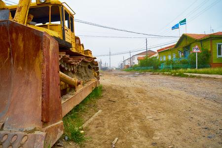Old rusty crawler bulldozer and administration building on the street of north yakutian settlement Chokurdakh photo