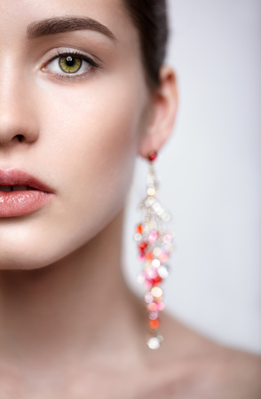 Half face close-up portrait of young brunette woman with red earrings in bokeh photo