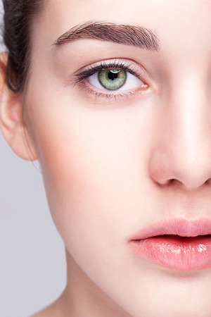 Close-up shot van vrouwelijk gezicht met dag make-up en groene pistache kleur ogen Stockfoto