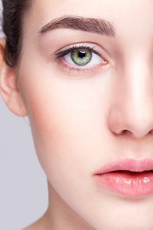 Closeup shot of female face with day makeup and  green pistachio colour eyes Foto de archivo
