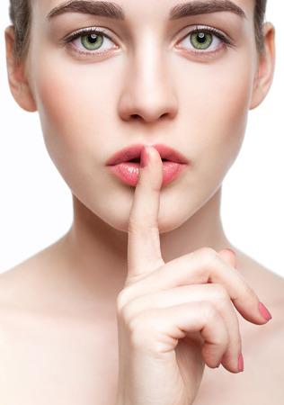 Portret van jonge mooie vrouw met groene pistache kleur ogen en de vinger op de lippen Stockfoto