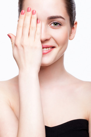 Green-eyed young beautiful woman in black dress closing eye by hand and smiling Standard-Bild