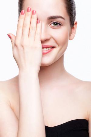 Groen-eyed mooie jonge vrouw in zwarte kleding sluiten oog met de hand en glimlachen