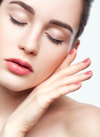 Retrato de joven bella mujer con los ojos cerrados y la mano con manicura rosa cerca de la cara