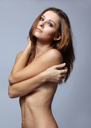 topless brunette: Young pretty topless woman posing on gray background Stock Photo