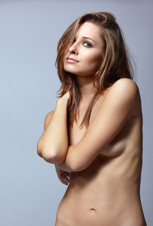 nude pose: Young pretty topless woman posing on gray background Stock Photo