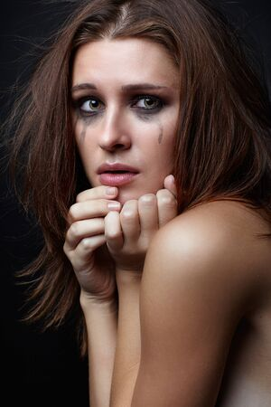 Young pretty woman with smeared mascara crying on black background photo