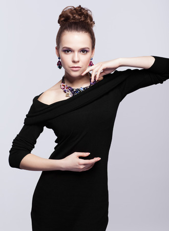 bead jewelry: Brown-haired young woman in black dress and with bijouterie on gray background