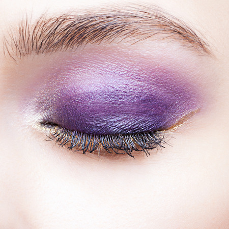 and eyelid: Closeup shot of woman closed eye and brows with violet eyelid day makeup