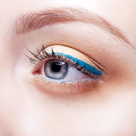 Closeup shot of woman eye with day makeup and blue arrow Foto de archivo