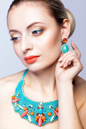 tucker: Beautiful blonde woman in bijouterie  on grey background Stock Photo