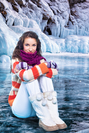 Young woman sitting on ice of siberian Baikal Lake in winter photo