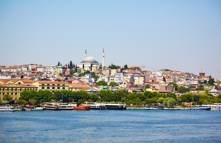 islamic scenery: The view across Golden Horn on the shore with residental buildings and Yavus Sultan Selim Mosque on the top of the hill, Istanbul, Turkey