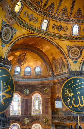 justinian: ISTANBUL, TURKEY - JULY 9, 2014: The interior view of the Hagia Sophia with 2 gigantic circular-framed medallions with the names of Muhammad and Allah  and Christian Mosaic image of the Virgin  and Archangel Gabriel in the apse  on the top of the main dom