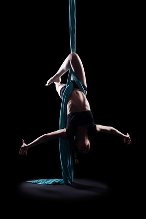 background isolated: Young woman gymnast with blue gymnastic ribbon isolated on black Stock Photo