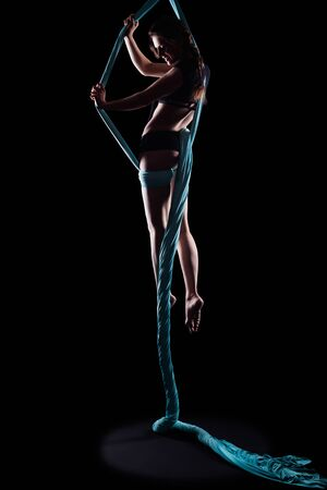 woman black background: Young woman gymnast with blue gymnastic ribbon isolated on black Stock Photo