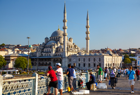 istanbul: ISTANBUL TURKEY  JULY 9 2014: A fishmen on Galata Bridge in front of Yeni Cami New MosqueIstanbul Turkey Editorial