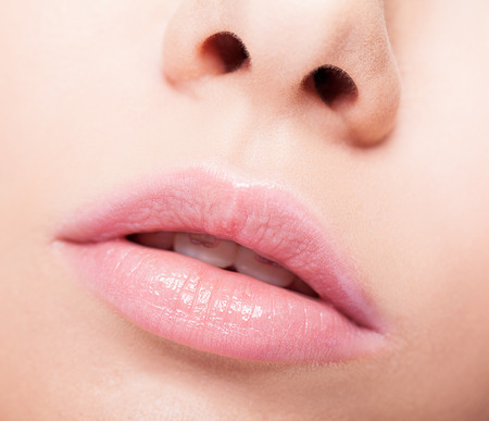 Closeup of woman open mouth with pink lips and brackets photo