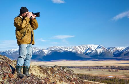 north ridge: Photographer in Altai mountains taking picture of North Chuisky Ridge Stock Photo