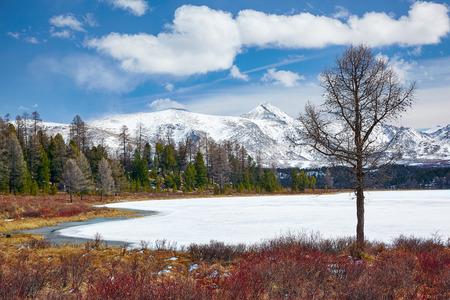 ulagan: Altai Lake Kodelyukyol in Ulagan region under ice with Kuraisky ridge on background Stock Photo