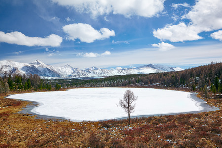 ulagan: Altai Lake Kodelyukyol in Ulagan region under ice with Kuraisky ridge on background Stock Photo
