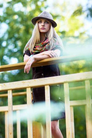 kerchief: Young pretty woman on small wooden bridge Stock Photo