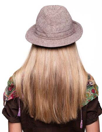 hair back: Studio portrait of young woman with long hair in hat from back side
