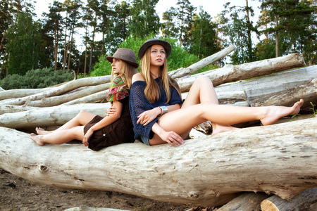 Two young pretty women on logs in the forest