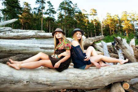 young girl barefoot: Two young pretty women on logs in the forest