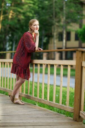 handrail: Young pretty woman on small wooden bridge with cottage in background Stock Photo