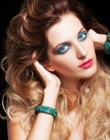 makeup eyes: Portrait of young beautiful woman with curly shaggy hair style and blue eyes make-up on black background