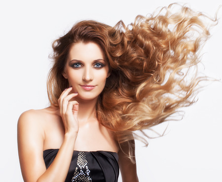 flyaway: Portrait of young beautiful smiling woman with curly shaggy fly-away hair on gray background