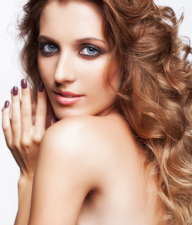 hairy back: Portrait of young beautiful woman with curly shaggy hair style with smoky eyes make-up on gray background