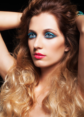 hairy arms: Portrait of young beautiful woman with curly shaggy hair style and blue eyes make-up on black background