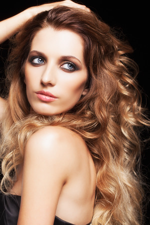hair style: Portrait of young beautiful woman with curly shaggy hair style on black background Stock Photo