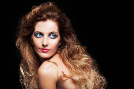 shaggy: Portrait of young beautiful woman with curly shaggy hair style and blue eyes make-up on black background