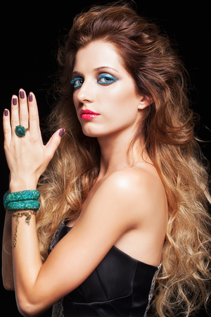 hair style: Portrait of young beautiful woman with curly shaggy hair style and blue eyes make-up on black background