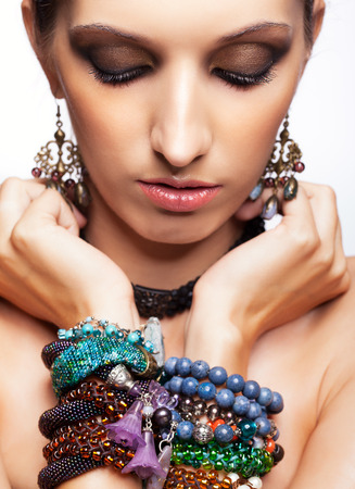 pretty eyes: Portrait of young pretty woman with bijouterie on hands and closed eyes