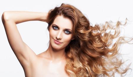 axila: Retrato de la mujer sonriente joven hermosa con el pelo rizado hirsuto pelo suelto sobre fondo gris