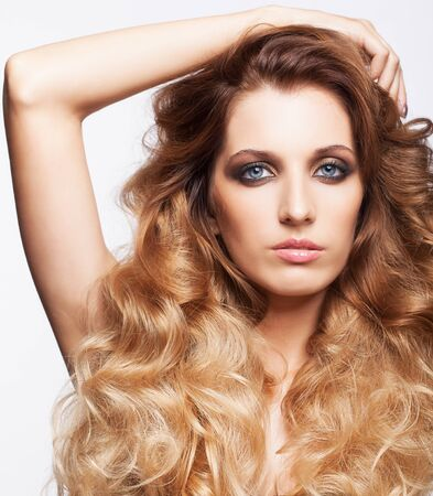 tousled: Portrait of young beautiful woman with curly shaggy hair style with smoky eyes make-up on gray background