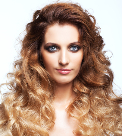 gray eyes: Portrait of young beautiful woman with curly shaggy hair style with smoky eyes make-up on gray background