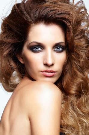 hair style: Portrait of young beautiful woman with curly shaggy hair style with smoky eyes make-up on gray background