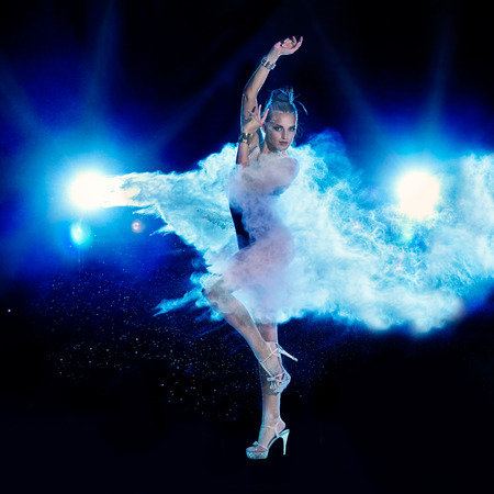 scatter: Young woman jumping in blue powder cloud on black background